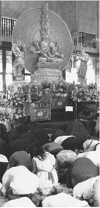 Worshippers bowing before Buddha in Singapore, 1989.