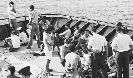 Dominican refugees are taken from a sailboat in the waters off the Florida Keys and boarded on a U.S. Coast Guard cutter before being interviewed by immigration officials. Many natives of the Dominican Republic left the island in reaction to the oppressio