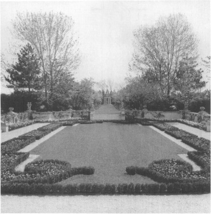Formal garden design with rectangualr middle with small shrub borders and grass in the center.