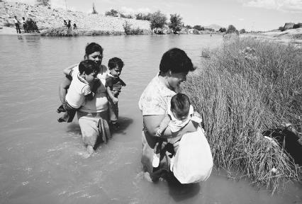 Mexican emigrants, with children in hand, cross the Rio Grande River. © Danny Lehman/Corbis.